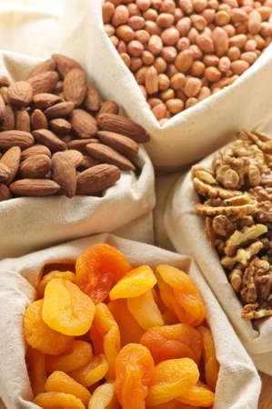Close-up of assorted nuts and dried apricots in jute bags. Stock Photo - 9569349