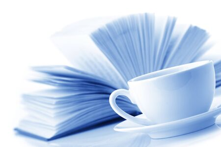 blue toned: White cup of coffee and open book on white background. Monochrome toned image.