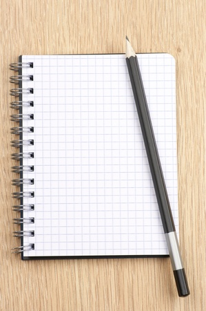 Spiral notepad with blank page and pencil on wooden desk. View from above. Stock Photo - 9569514