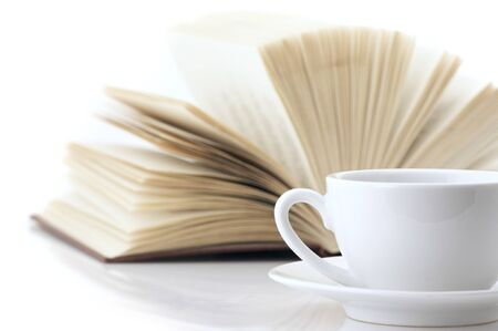 White cup of coffee and open book on white background.