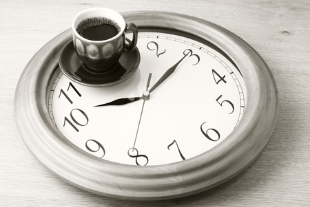 Coffee time: cup of coffee on clock dial. Sepia. Stock Photo
