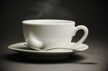 cup saucer: Cup of hot coffee with steam on dark background. Toned image.