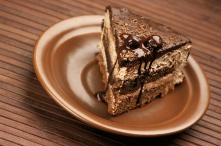 slice cake: Torta al cioccolato artigianale nel piatto in ceramica marrone sulla superficie di legno marrone.
