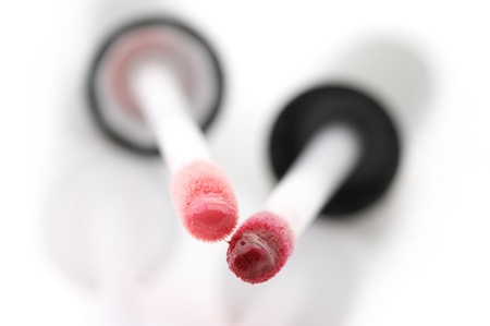 Close-up of two applicators with various lip gloss on white background. photo