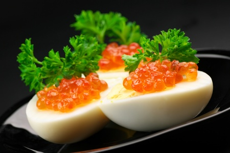 Canapes with egg, salmon caviar and parsley on black plate against dark background.. photo