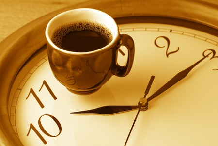 coffee time: Coffee time: cup of coffee on clock dial. Monochrome toned image.