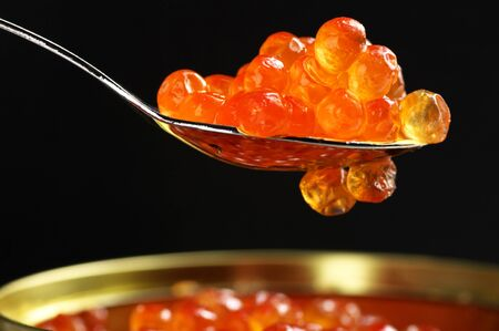 Canned salmon caviar with spoon close-up on black background. photo