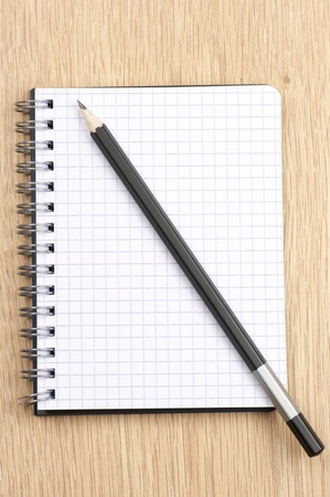 Spiral notepad with blank page and pencil on wooden desk. View from above. Stock Photo - 9825237