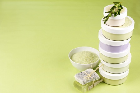 Jars of various cosmetic cream, bath salt and natural homemade soap on green background. photo