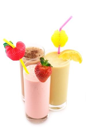 yaourts: Trois assortiment de cocktails de protéine avec les pailles et les décorations isolées sur fond blanc.