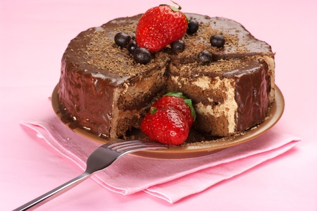 an icing: Homemade chocolate cake with strawberries and fork on pink background.. Stock Photo