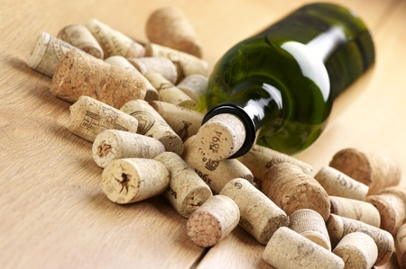closed corks: Closed wine bottle and heap of used corks on wooden surface.