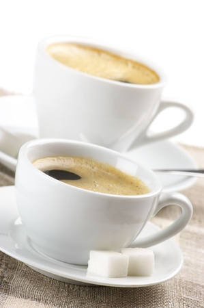 coffee spoon: Close-up of two white cups of coffee with froth on linen napkin against white background. Stock Photo