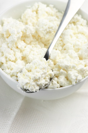 시골집: 그릇에 코 티 지 치즈와 숟가락의 근접.