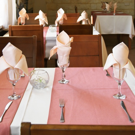 Part of restaurant with table set on foreground. photo