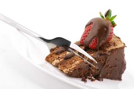 Slice of chocolate cake with strawberry and fork in white plate on white background.