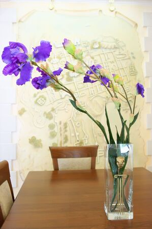 purple irises: Bouquet of violet irises in glass vase on wooden table in beige interior. Stock Photo