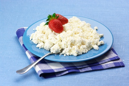 Cottage cheese with strawberries and cream in blue plate with checked napkin on blue tablecloth. photo