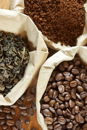 pile of leaves: Close-up of assorted coffee and green tea in paper bags.