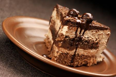 porcion de torta: Primer plano de pastel de chocolate casera en placa cerámica marrón. Foto de archivo