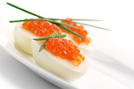Canapes with egg, salmon caviar and onion. photo