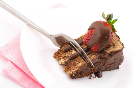 Slice of chocolate cake with strawberry and fork in white plate with pink napkin on white background.