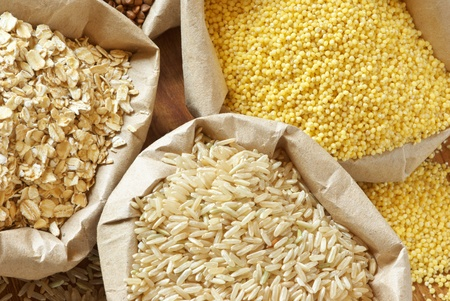 org�nico: Primer plano de cereales surtidos en bolsas de papel.