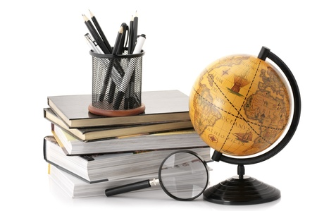 Vintage globe, stack of books and office supplies isolated on white background. photo