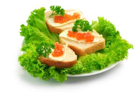 Canapes with butter and salmon caviar on lettuce leaves against white background. photo