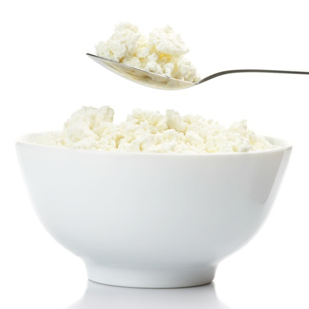 Bowl and spoon with cottage cheese against white background.