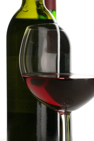 Two bottles and glass of red wine close-up on white background.