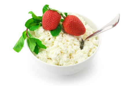 Cottage cheese with mint and strawberries in white bowl isolated on white background.