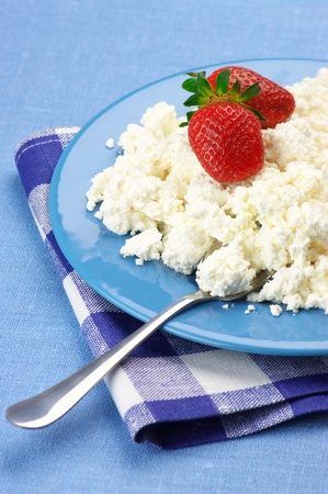 Cottage cheese with strawberries in blue plate with checked napkin. photo