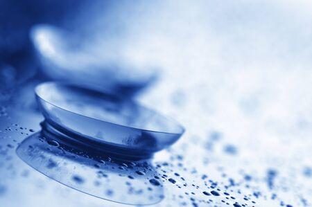 lentes contacto: Primer plano de dos lentes de contacto con gotas sobre fondo claro. Imagen tonificada azul. Foto de archivo