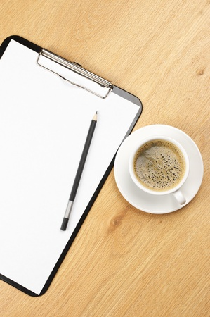 Clipboard with blank page and cup of coffee on wooden desk. View from above. Stock Photo - 10547884