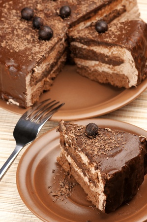 Close-up of homemade chocolate cake and fork on beige mat. photo
