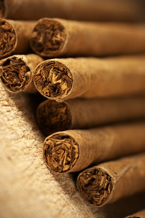 Heap of cigars on old wooden surface.