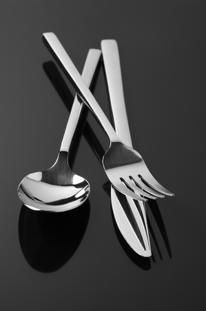 Set of steel fork, knife and spoon on dark background. Stock Photo