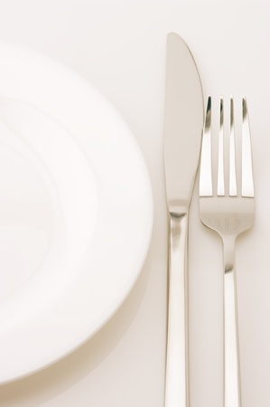 Empty white plate, knife and fork on light background. Toned image. Stock Photo - 10751911