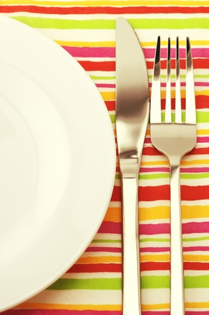 Fork, knife and empty plate on colorful striped tablecloth.