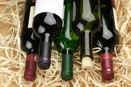 red straw: Stack of various wine bottles lying on straw.