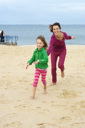 outdoor pursuit: Happy mother and daughter running at beach.