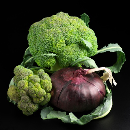 raw vegetables: Raw broccoli and red onion on black background. Stock Photo