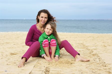 Happy mother and daughter resting at beach. photo