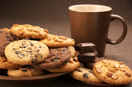 chocolate chips cookies: Assorted cookies in brown plate and brown mug of coffee on brown canvas.