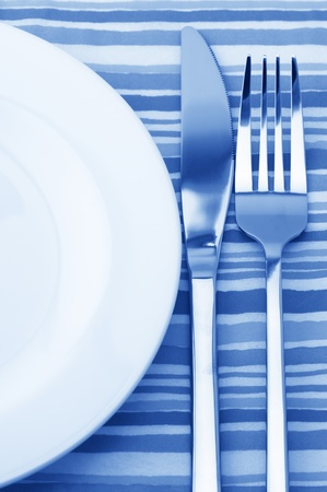 Fork, knife and empty plate on striped tablecloth. Blue toned image. photo