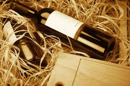 Two wine bottles lying in wooden box with straw. Monochrome toned image. photo