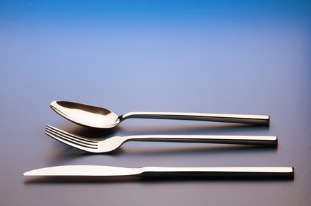 Steel fork, knife and spoon on blue background with copy space. Stock Photo - 11089070