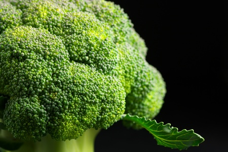 Close-up of raw broccoli on black background.