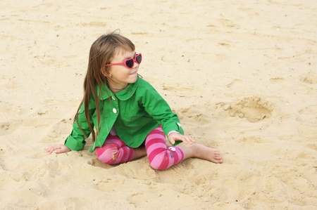 Small cute girl playing on sand at beach. photo